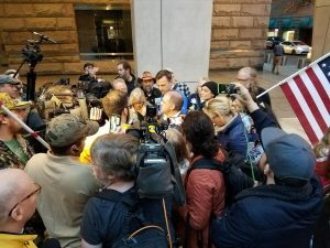 Marcus Mumford surrounded by media after Bundy trial